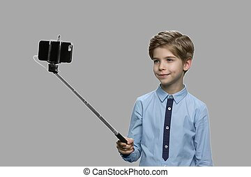 Cute little boy using selfie stick.