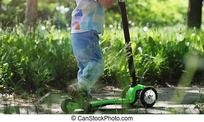 Cute little boy wearing cap riding mini scooter across the dandelions, kick scooter in the park in slow motion on sunny summer day. 1920x1080
