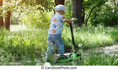 Cute little boy wearing cap riding mini scooter, kick scooter in the park on sunny summer day in slow motion. 1920x1080