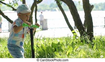 Cute little boy wearing cap riding mini scooter, kick...