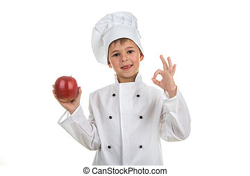 Cute little boy wearing chef uniform making ok gesture and holding red apple
