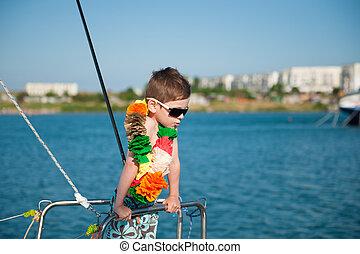 cute little boy wearing sunglasses and Hawaiian decoration aboard
