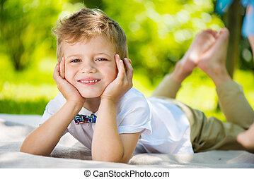 Cute little boy with butterfly lying on green grass