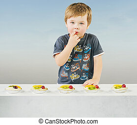 Cute little boy with delicious fruit cake
