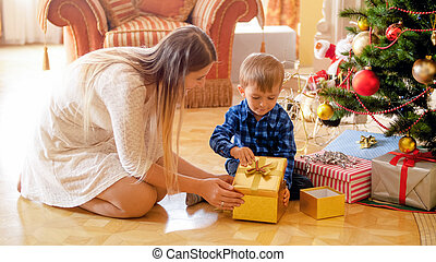Cute little boy with mother sitting under Christmas tree and open gift box