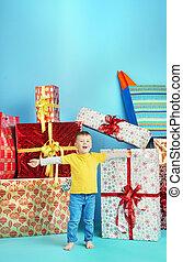Cute little boy with plenty of gifts