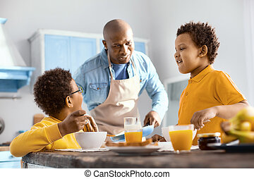 Cute little boys chatting with their father while eating breakfast