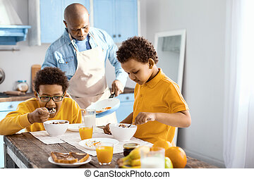 Cute little boys eating breakfast while their father cooking omelet
