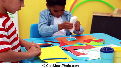 Cute little boys having art time in the classroom in...