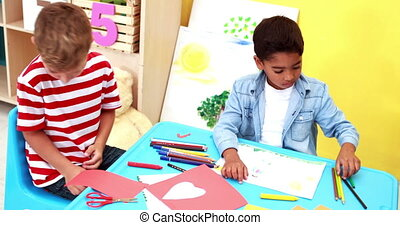 Cute little boys having art time in the classroom waving to...