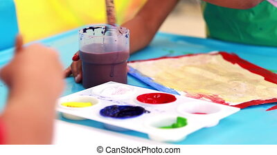 Cute little boys painting at table