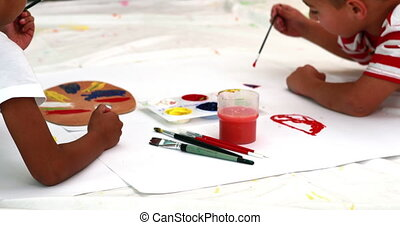 Cute little boys painting lying on paper in playschool