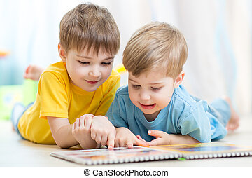cute little boys read book together