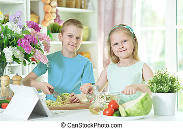 Cute little brother and sister cutting vegetables