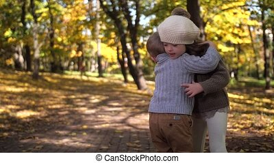 Cute little brother and sister hugging in nature