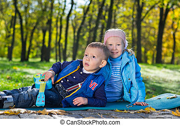 Cute little brother and sister playing outdoors