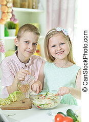 little brother and sister preparing salad together