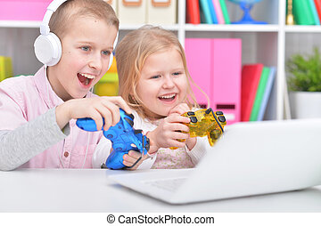 Cute little brother and sister using laptop