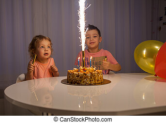Cute little brothers blowing out candles on birthday cake at party