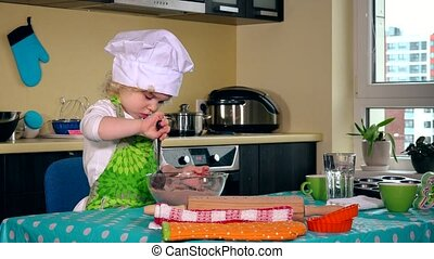 Cute little chef girl with white hat mixing flour for cake on table in kitchen