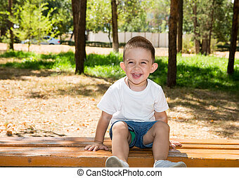 Cute little child boy in park on nature at summer. Use it for baby, parenting or love concept
