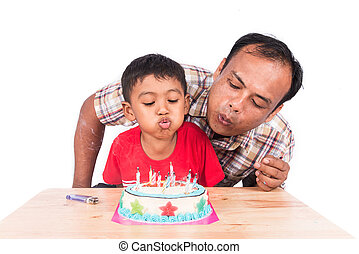 Cute little child boy with his father blowing birthday cake