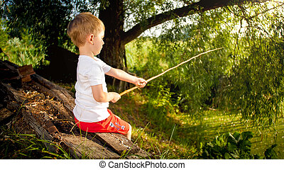 Cute little child fishing at pond on the sunset.