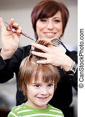 Cute little child getting a haircut