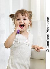 Cute little child girl brushing teeth in bathroom