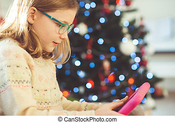 Cute little child girl playing with tablet near christmas tree