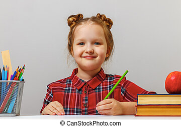 Cute little child girl sits at the table and draws. Gray background. Close-up.