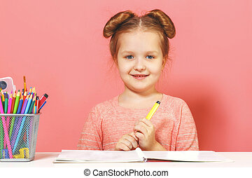 Cute little child girl sits at the table and draws. Pink background. Close-up