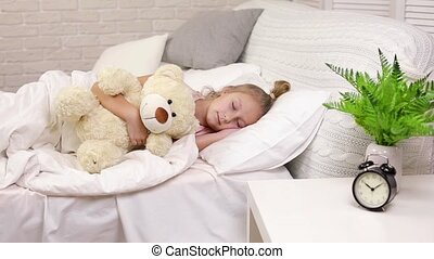 Cute little child girl sleeping with teddy bear