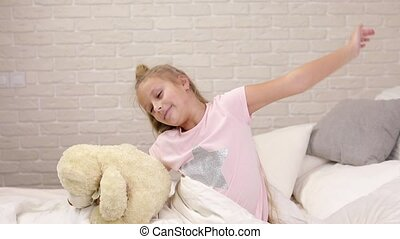 cute little child girl wakes up from sleep in bed - cute...