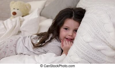 cute little child girl wakes up from sleep in bed - happy...