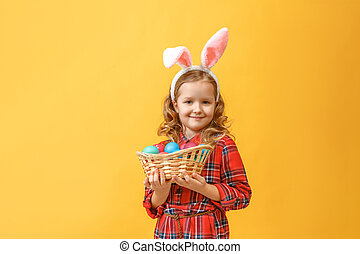 Cute little child girl with bunny ears holding basket of Easter eggs on a colored background.