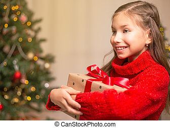 Cute little child girl with present gift box near Christmas tree at home.