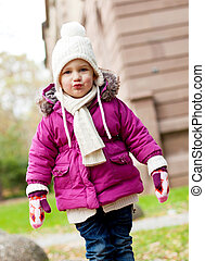 cute little child in pink jacket and hat outdoor