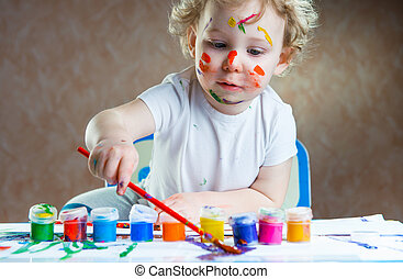 Cute little child painting with paintbrush and colorful...