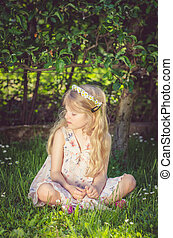 cute little child sitting in the grass