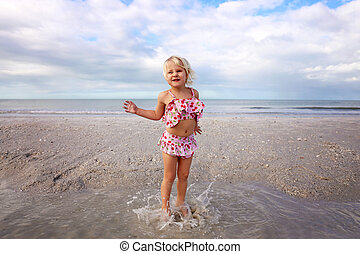 Cute Little Child Splashing and Playing in the Water on the Beach by the Ocean