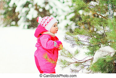Cute little child walking in snowy winter forest