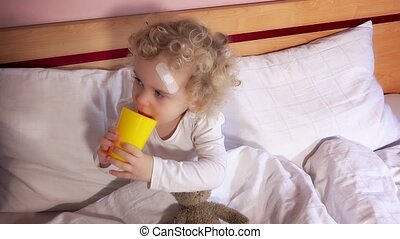 Cute little child with adhesive bandage on head drinking water from cup
