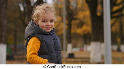 little child with blonde curly hair in autumn park area, medium portrait of funny smiling boy
