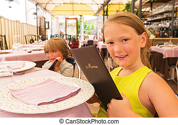 Cute little children choosing their meal in a kid's menu in a restaurant