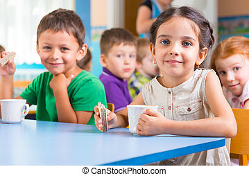 Cute little children drinking milk at daycare