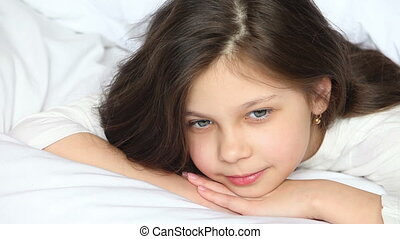 Cute little girl 8 years on a bed,