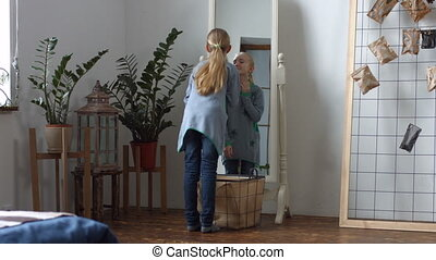 Cute little girl admiring her reflection in mirror