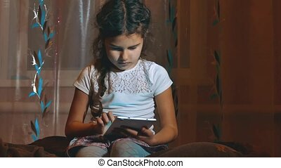 Cute little girl alone with tablet computer at night in a...