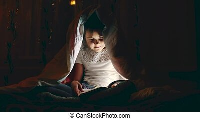 Cute little girl alone with tablet computer under blanket at...